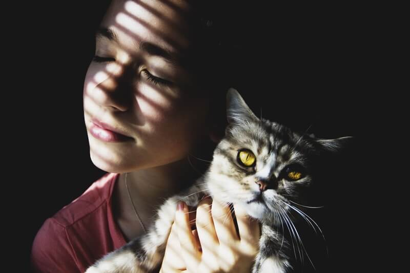 how much does preventive care coverage cost _ woman holding a cat with yellow eyes