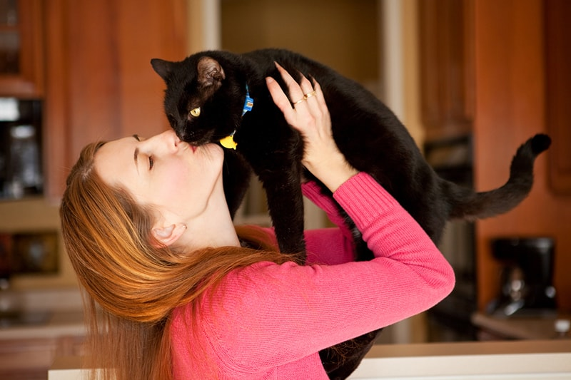 tips to prevent zoonotic diseases in cats and dog _ woman cuddling black cat