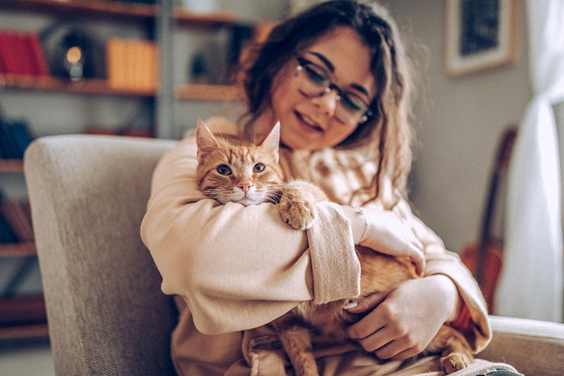 what pet health insurance covers _ young woman holding an orange tabby cat