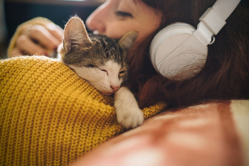 professional help for depressed cats _ cat being held by girl in a yellow sweater with white headphones
