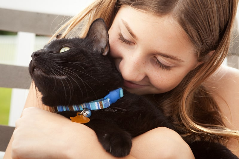 top tips for feeding a cat _ brunette girl hugging her black cat