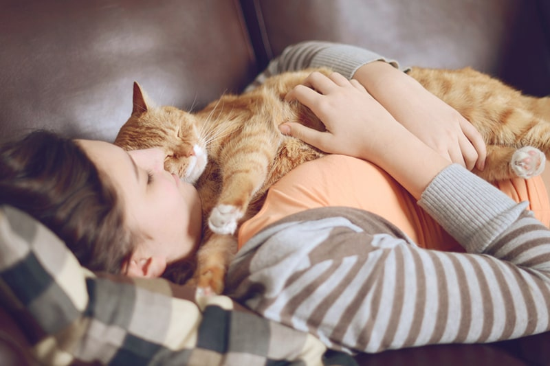 how to save on cat costs _ woman cuddling with an orange tabby cat on a brown leather sofa