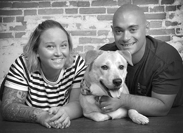 Two ASPCA Pet Health Insurance customers pose with their dog in front of a brick wall