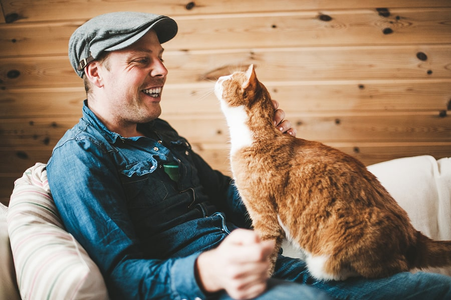 man in a newsboy cap laughing with his ginger cat on a cream sofa