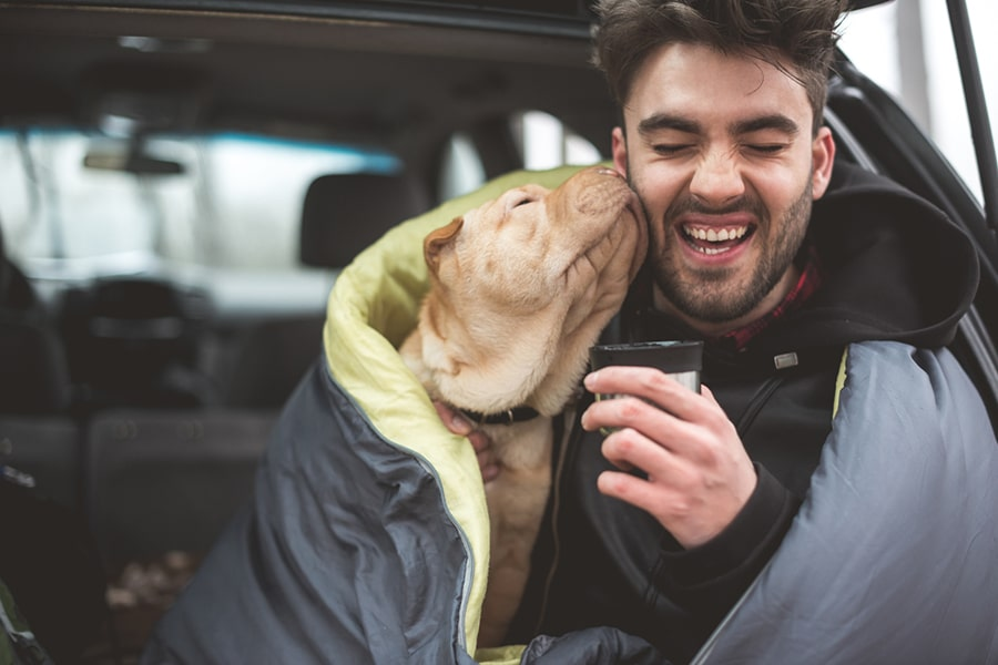 man being licked on the face by a shar pei while sitting in the open hatchback of a car and drinking coffee