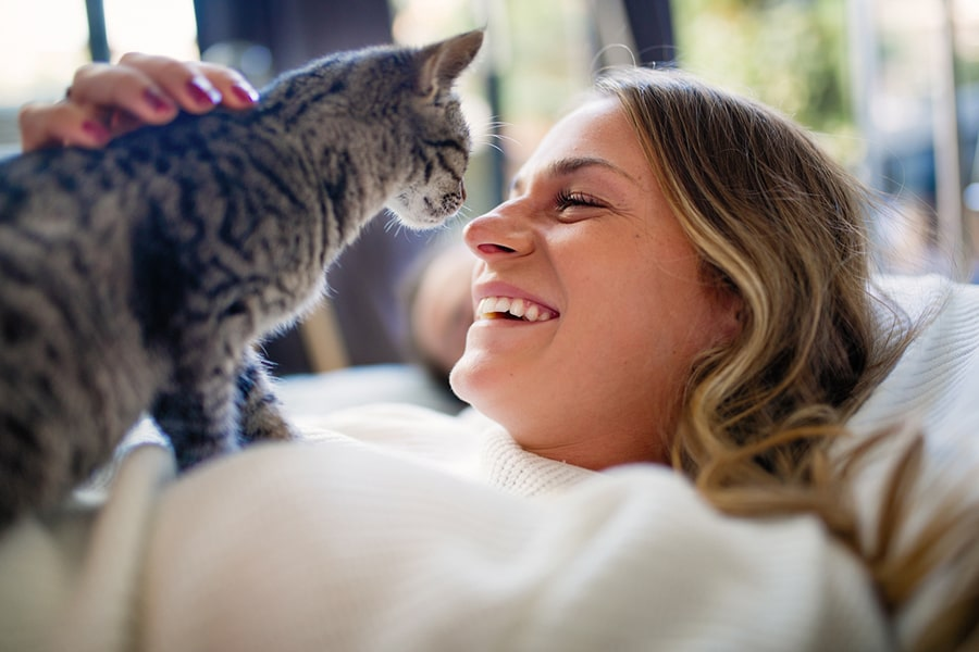 young blonde woman laughing with a tabby cat