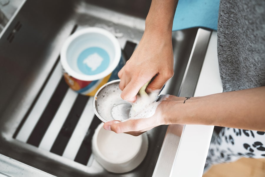 pet owner cleaning food bowls in the sink