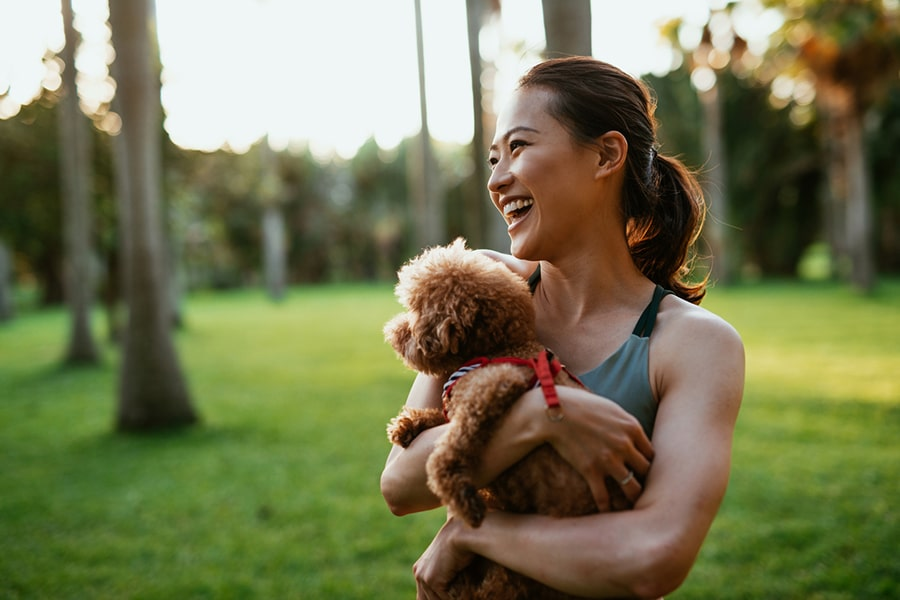 woman in athletic workout clothing holding a small dog in a park